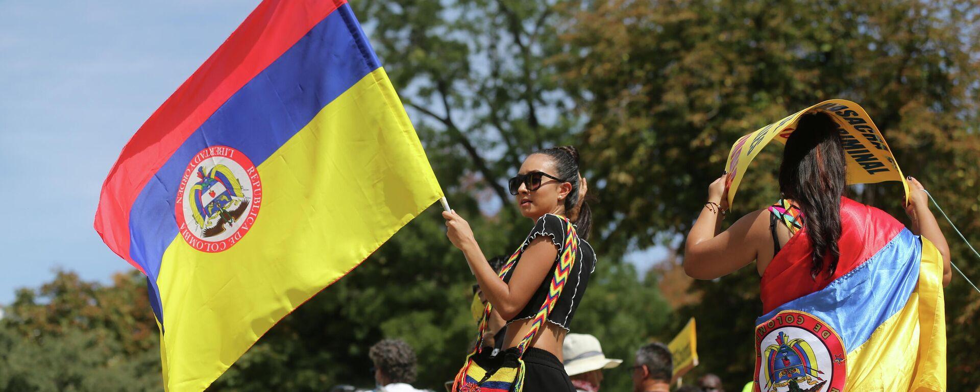 Una chica sostiene bandera de Colombia durante una manifestación contra la llegada del presidente del país a Madrid - Sputnik Mundo, 1920, 13.09.2021