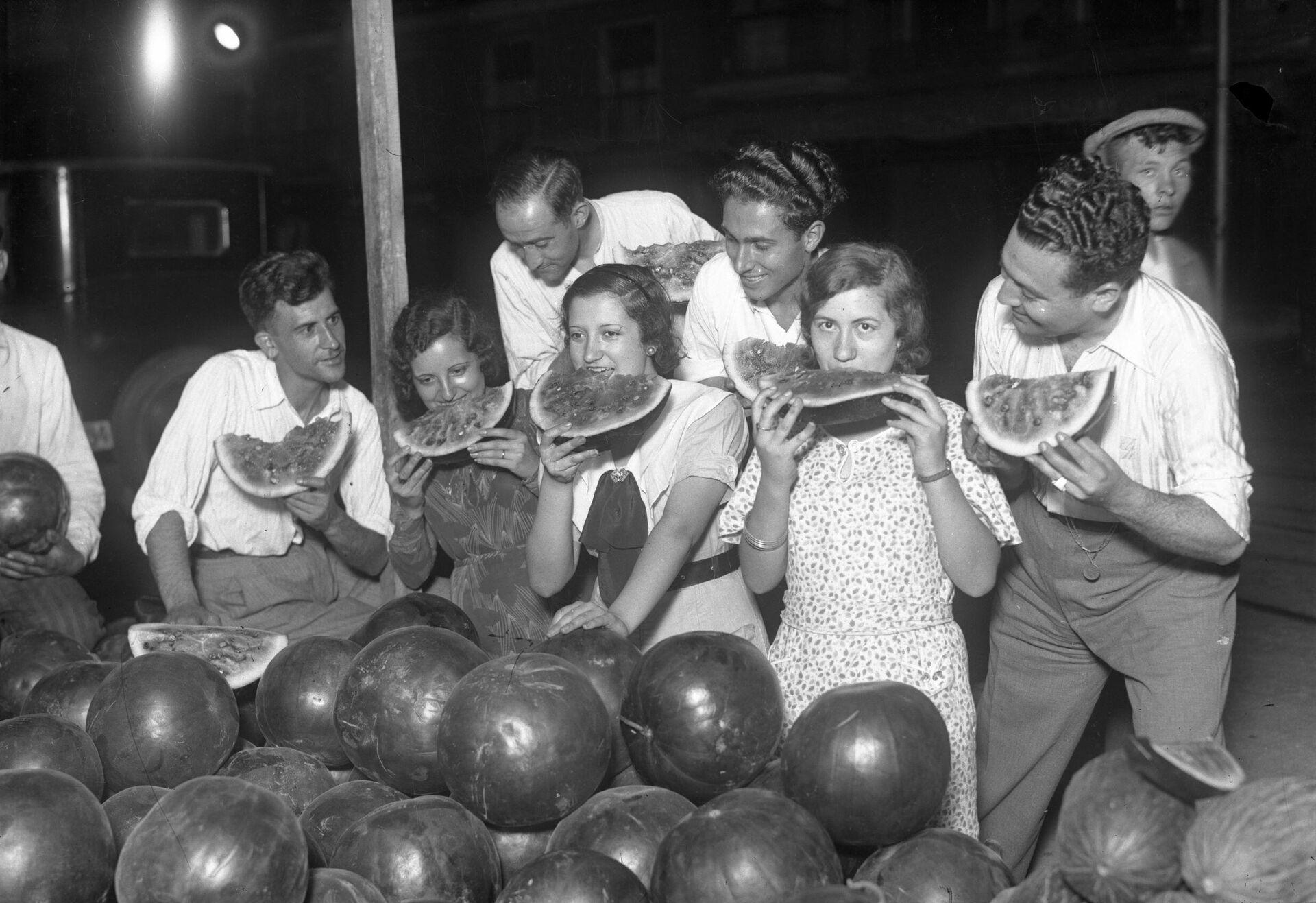 Grupo de jóvenes degustando sandías en un puesto callejero. Madrid, 1935 - Sputnik Mundo, 1920, 17.09.2021