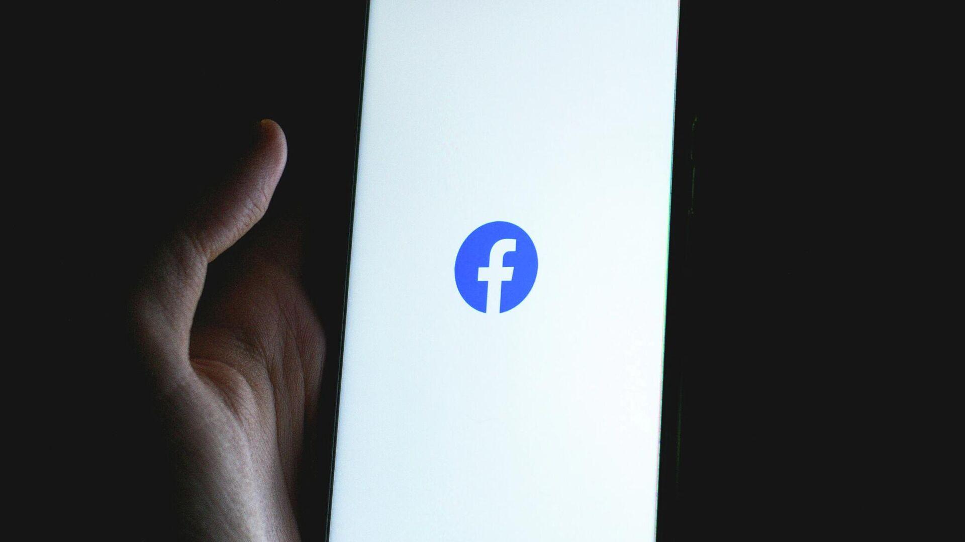 Una persona sostiene un teléfono con el logotipo de Facebook - Sputnik Mundo, 1920, 15.09.2021