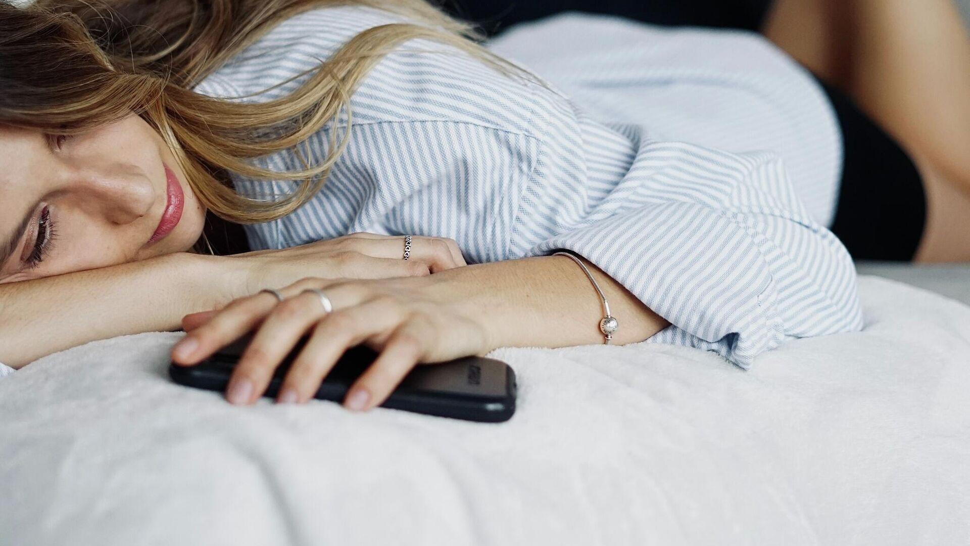 Una persona en la cama con un teléfono en la mano - Sputnik Mundo, 1920, 16.09.2021