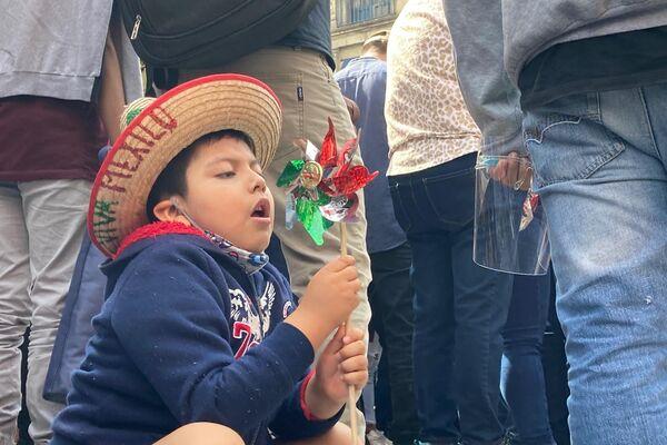 Un niño espera el inicio del desfile militar jugando con un rehilete con los colores de la bandera mexicana - Sputnik Mundo