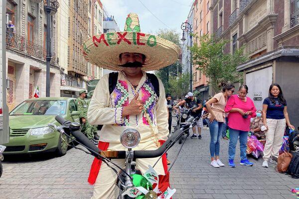 Un hombre ataviado con un sombrero de paja durante el desfile militar  - Sputnik Mundo