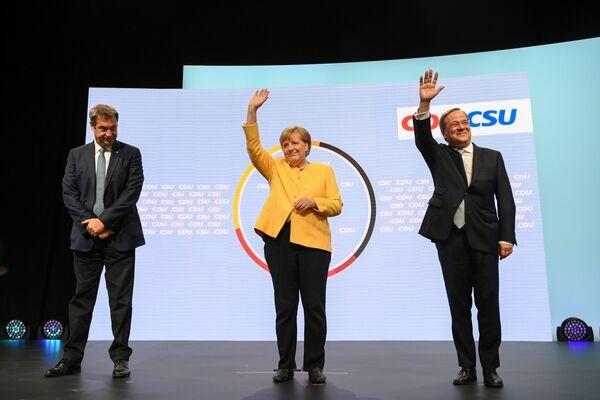 Tres principales candidatos para el puesto de canciller son: Annalena Baerbock, de 40 años, la diputada del Bundestag, la presidenta del partido Die Grünen (Los Verdes); Armin Laschet, de 60 años, ministro presidente del Land de Renania del Norte Westfalia, que se ocupa el puesto del presidente de la CDU desde enero; Olaf Scholz de 63 años, vicepresidente y actual ministro de Finanzas que representa la SPD. Angela Merkel no participa en las elecciones por primera vez desde 2005. Ella anunció su decisión en el otoño de 2018, después de una serie de elecciones regionales fallidas, donde la CDU mostró malos resultados.En la foto: presidente de la CSU, Markus Soder, la canciller de Alemania, Angela Merkel, y el candidato al cargo de canciller de la coalición CDU-CSU, Armin Laschet. - Sputnik Mundo