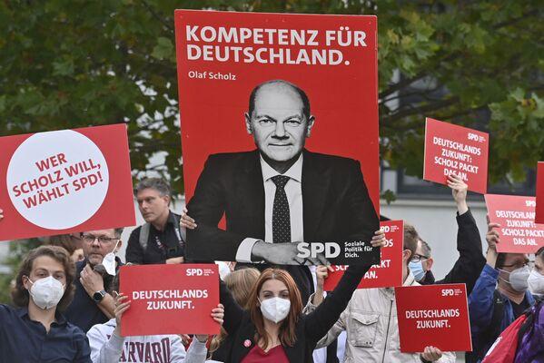 La principal sorpresa de esta campaña electoral es el liderazgo de los socialdemócratas: les apoyan el 26% de los votantes. En muchos sentidos, este es el mérito de Olaf Scholz. Su índice de aprobación personal es del 54%, es el segundo político más popular del país después de Merkel.En la foto: partidarios de Olaf Scholz esperan su aparición antes de un debate de televisión electoral en Berlín, Alemania. - Sputnik Mundo