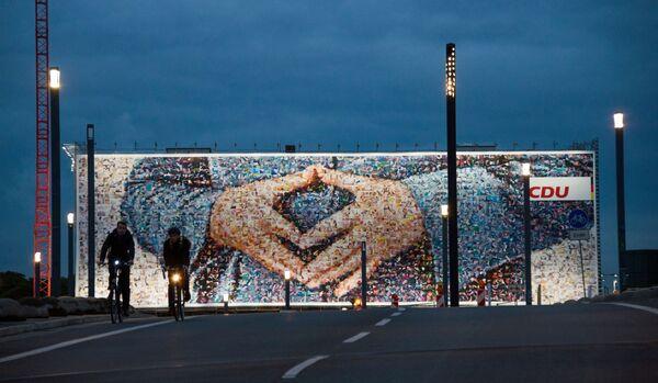 El cartel electoral representa el gesto famoso de Angela Merkel, la canciller de Alemania, en Berlín. - Sputnik Mundo