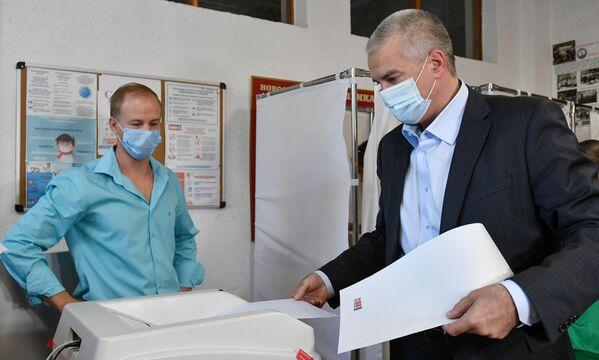 El presidente de la República Autónoma de Crimea, Serguéi Axiónov, entrega su voto en un colegio electoral de la ciudad de Simferópol. - Sputnik Mundo
