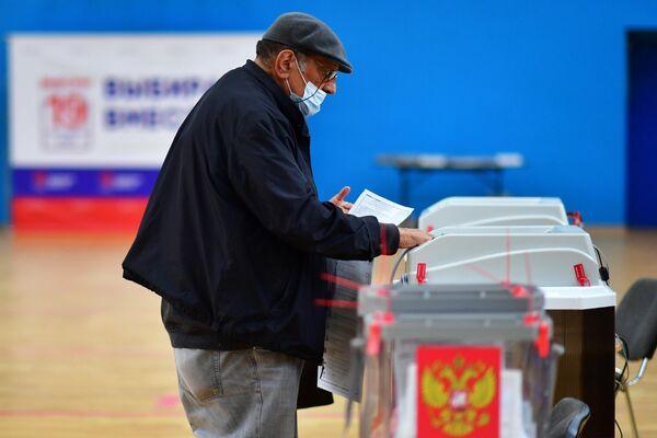 Un hombre vota en uno de los colegios electorales de Moscú. - Sputnik Mundo