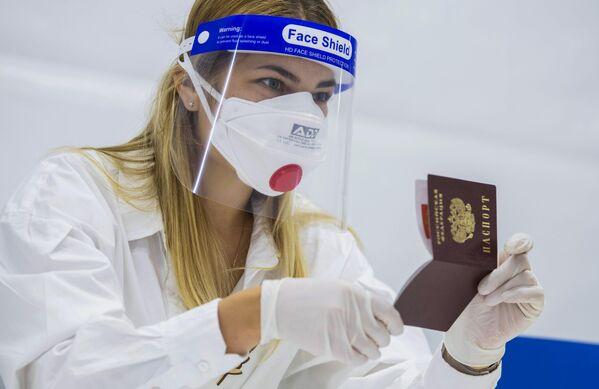 Trabajadora de uno de los colegios electorales revisa el documento de identidad de un votante. - Sputnik Mundo