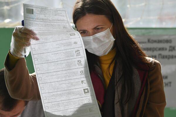 Una mujer busca su candidato en la papeleta electoral. - Sputnik Mundo