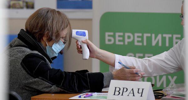 Medición de la temperatura de una ciudadana antes de entrar en el colegio electoral. - Sputnik Mundo