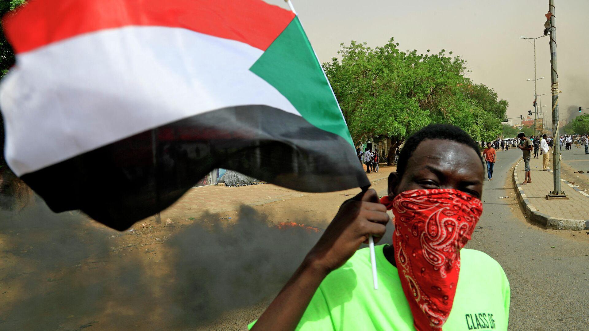 Un manifestante con la bandera de Sudán (archivo) - Sputnik Mundo, 1920, 21.09.2021