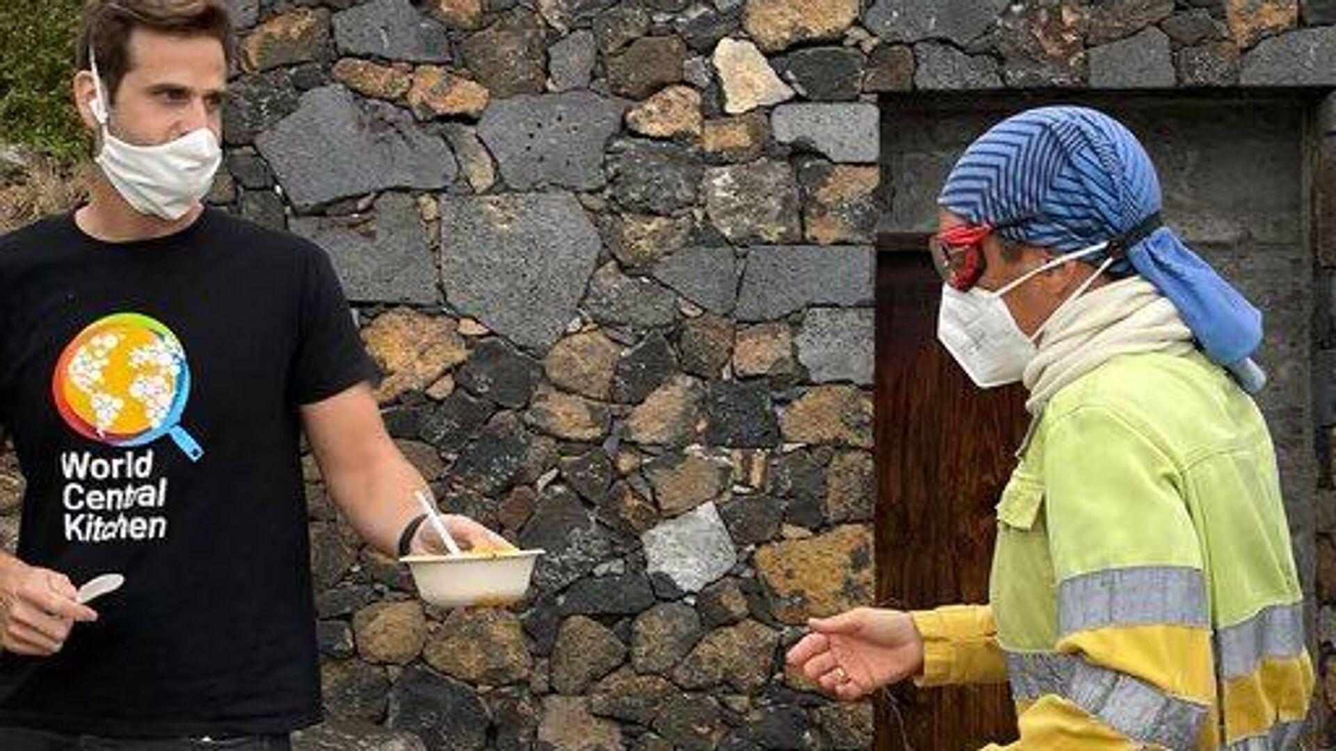 Un voluntario de World Central Kitchen ofreciendo comida a uno de los trabajadores del volcán de La Palma - Sputnik Mundo, 1920, 23.09.2021