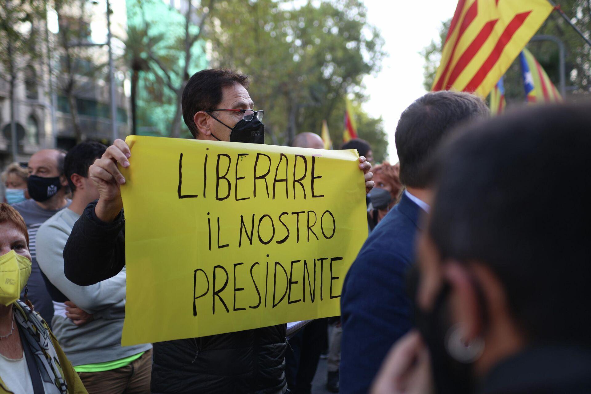 Un hombre muestra una pancarta en italiano en la manifestación para protestar por la detención de Puigdemont - Sputnik Mundo, 1920, 24.09.2021