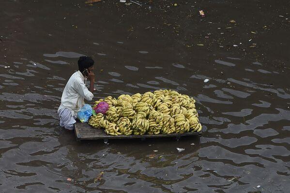 Un vendedor de fruta transporta su mercadería en una calle inundada por las fuertes lluvias en Lahore, Pakistán. - Sputnik Mundo