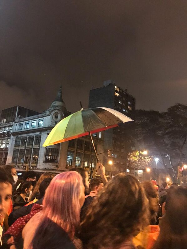Un paraguas se eleva entre la multitud, luego de que comenzara a llover levemente.  - Sputnik Mundo