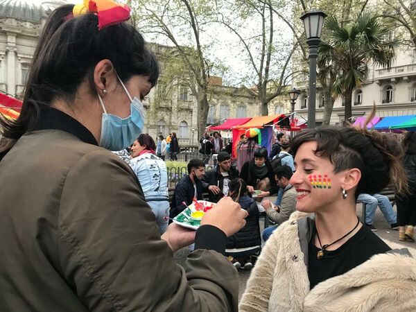 Una joven le pinta a otra una mejilla con los colores de la diversidad. - Sputnik Mundo