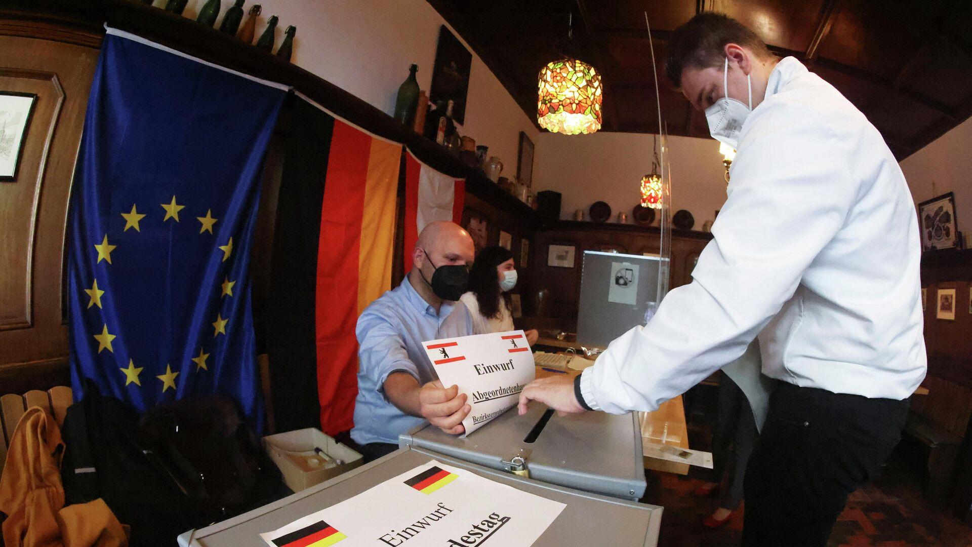 Un hombre emite su voto durante las elecciones parlamentarias en Alemania - Sputnik Mundo, 1920, 26.09.2021