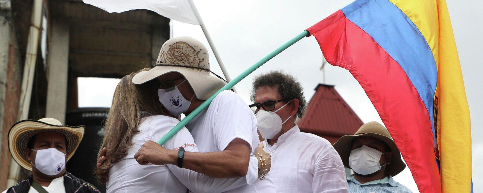 Rodrigo Granda, integrante del partido político FARC y excombatiente, se abraza con la familia de una víctima de la guerrilla en 2020 - Sputnik Mundo, 1920, 27.09.2021