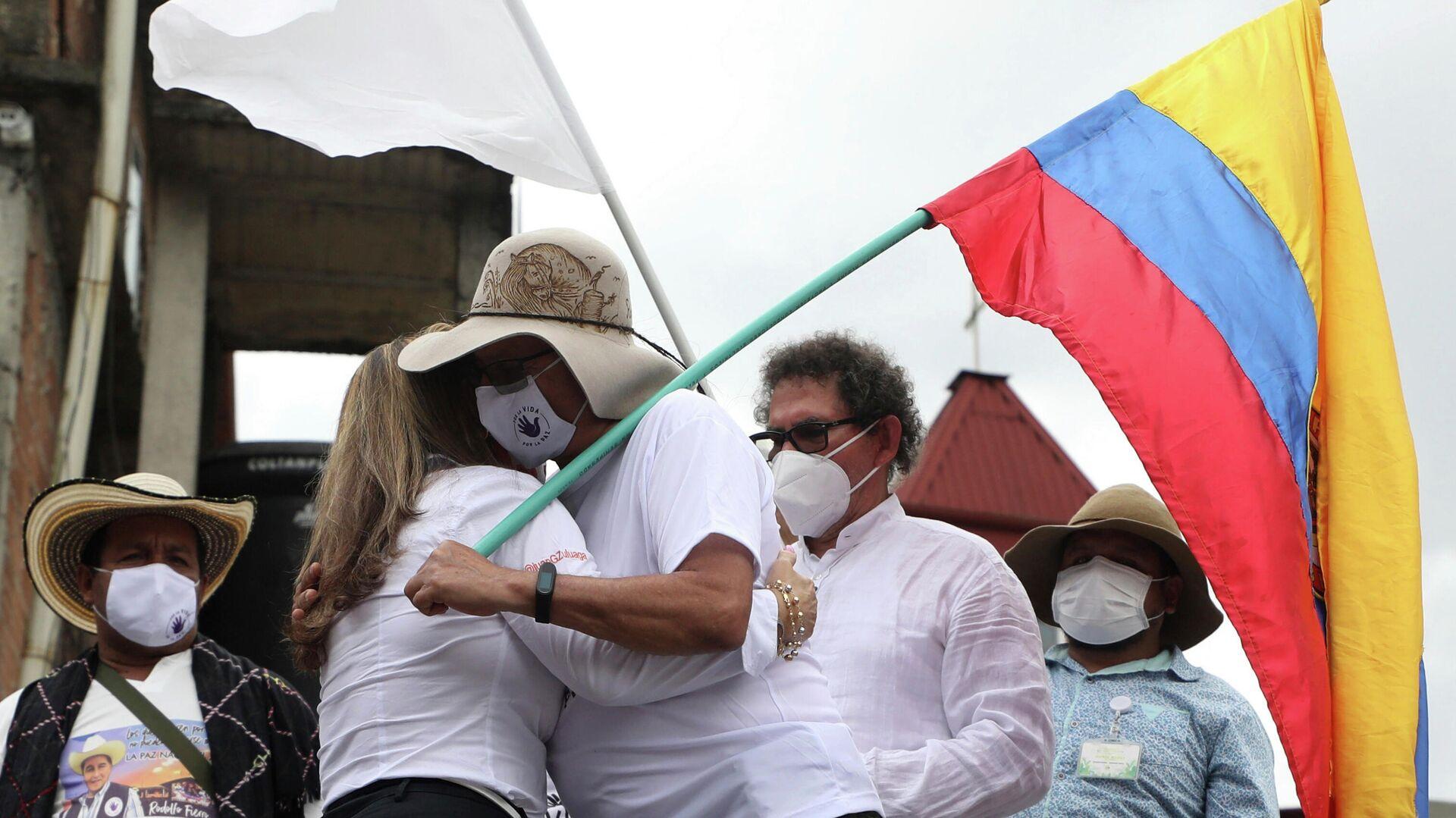 Rodrigo Granda, integrante del partido político FARC y excombatiente, se abraza con la familia de una víctima de la guerrilla en 2020 - Sputnik Mundo, 1920, 13.10.2021