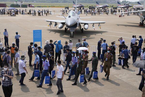 La mayor exposición en el ámbito de la aviación y espacio de China se celebra cada dos años, aunque en 2020 tuvo que ser cancelada debido a la pandemia. En la foto: militares extranjeros pasan cerca del caza ligero chino J-10C.  - Sputnik Mundo