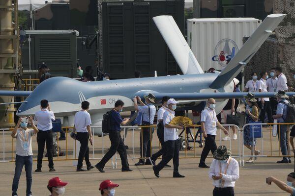 El salón aeronáutico recibió su nombre por la ciudad en que se celebra: Zhuhai, en la provincia sureña china de Guangdong.En la foto: unos visitantes pasan al lado del dron chino CH-4. - Sputnik Mundo