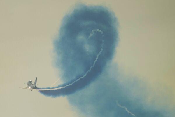 Un miembro del grupo acrobático 1 de Agosto, de la FFAA china, realiza un vuelo de demostración en un caza J-10 en el Salón Aeroespacial de Zhuhai. - Sputnik Mundo