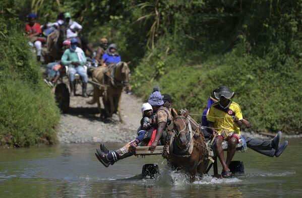 Migrantes procedentes de Haití cruzan un río en su camino hacia la frontera colombo-panameña en Akandi. - Sputnik Mundo
