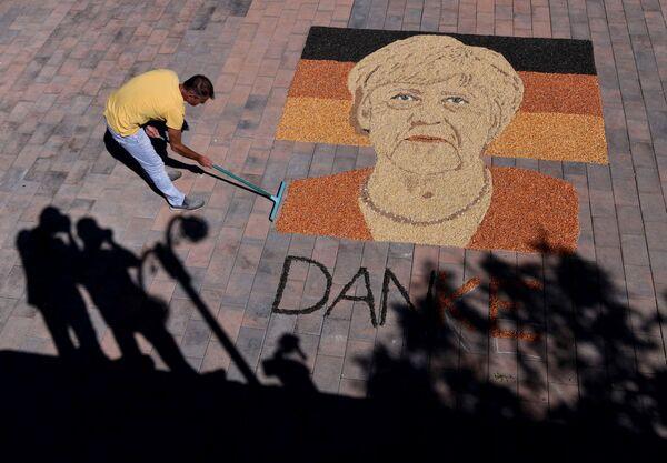 El artista kosovar Alkent Pozhegu termina un retrato de la canciller alemana Angela Merkel hecho con granos y semillas. - Sputnik Mundo