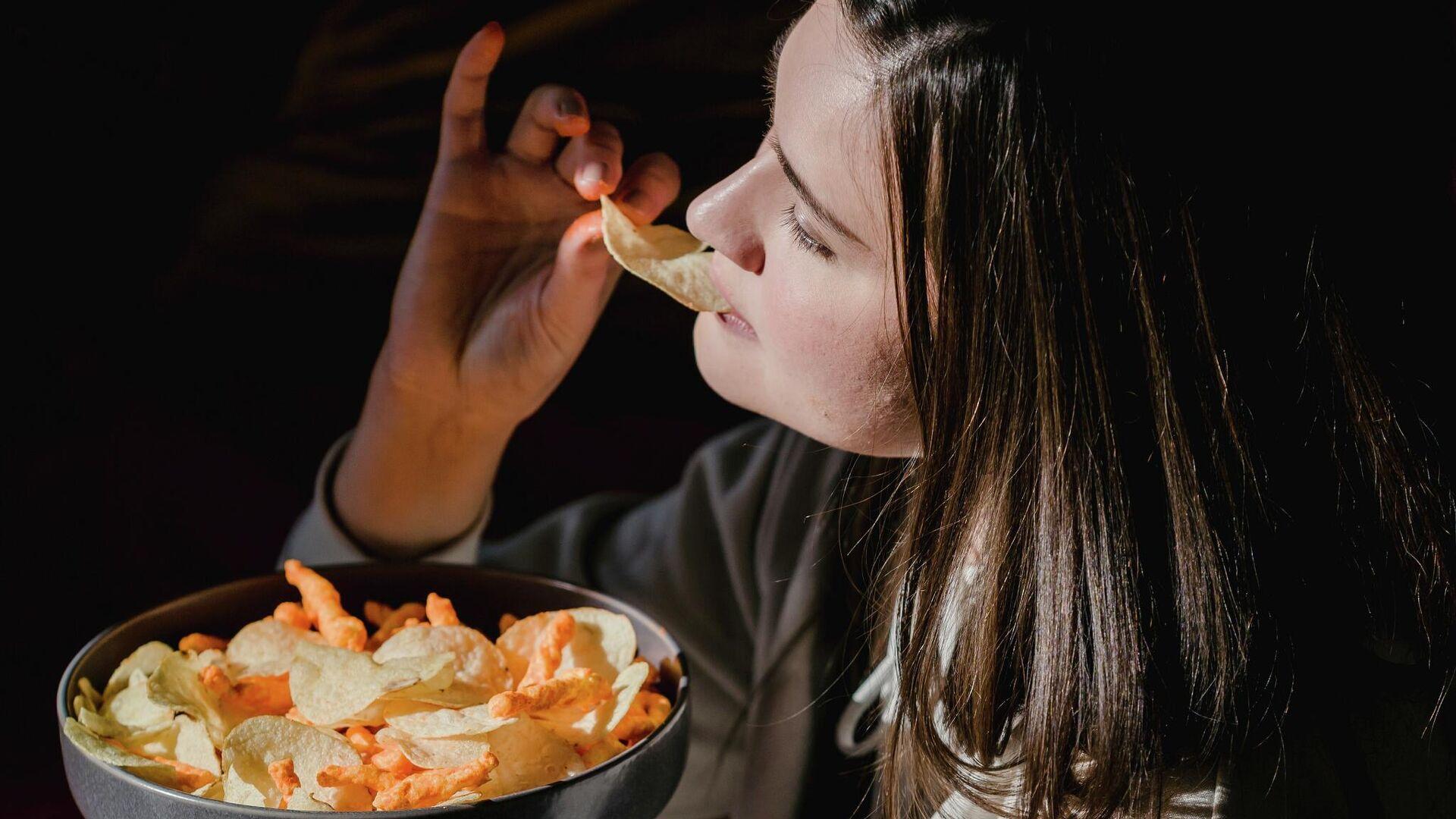 Una mujer comiendo comida chatarra - Sputnik Mundo, 1920, 01.10.2021