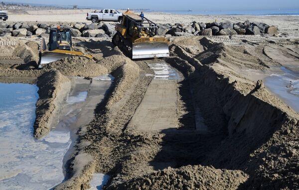 Trabajadores levantan barreras en la costa para evitar la expansión de la mancha de petróleo. - Sputnik Mundo