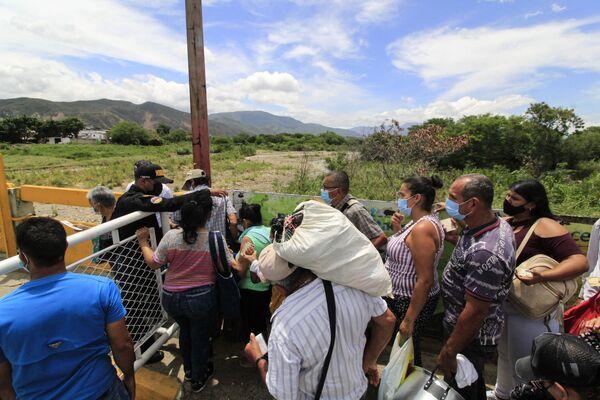 Unos venezolanos cruzan el Puente Internacional Simón Bolívar, ubicado entre la localidad de San Antonio del Táchira y la ciudad colombiana de Cúcuta. - Sputnik Mundo