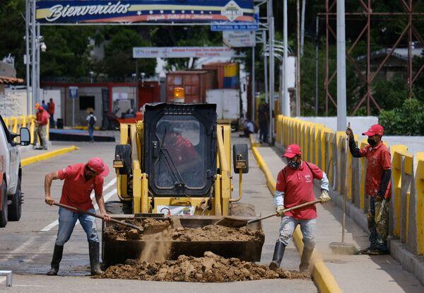 Unos trabajadores llenan un agujero que dejó uno de los contenedores en el puente Simón Bolívar. - Sputnik Mundo