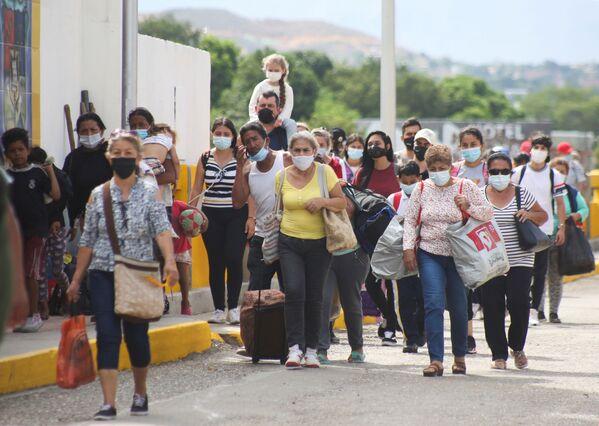 Unos colombianos autorizados para entrar en el país por razones humanitarias cruzan el puente Simón Bolívar. - Sputnik Mundo