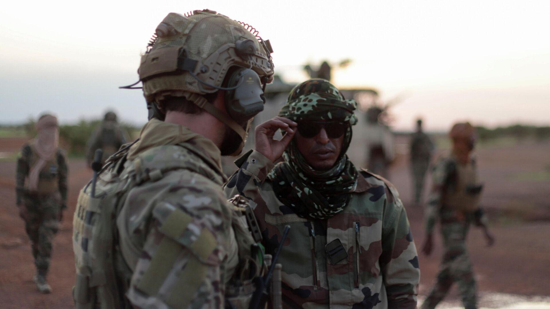 Un oficial de la Fuerza especial Takuba habla con un soldado de Malí durante una patrulla cerca de la frontera con Níger en Dansongo Circle, Mali - Sputnik Mundo, 1920, 06.10.2021
