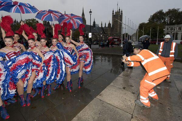 Un obrero toma una foto de un grupo de bailarinas del Moulin Rouge en el centro de Londres. - Sputnik Mundo