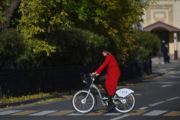 Una muchacha monta una bicicleta cerca del convento Novodevichy, un popular punto turístico de la capital rusa. - Sputnik Mundo
