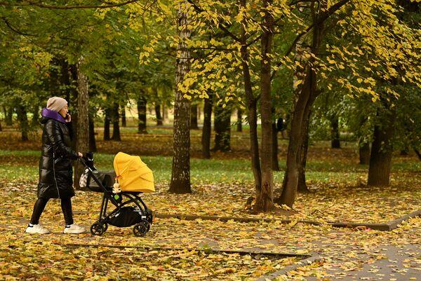 Una mujer con un cochecito de bebé camina en el parque Krasnaya Presnya en Moscú. - Sputnik Mundo