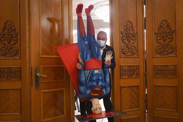 Un hombre sostiene de cabeza un maniquí parecido al de Superman antes de una votación de censura contra el primer ministro rumano, Florin Citu. - Sputnik Mundo