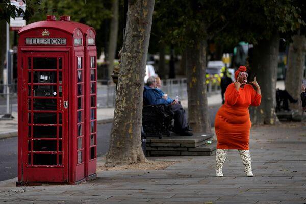 Una modelo posa cerca de una cabina telefónica en Londres. - Sputnik Mundo