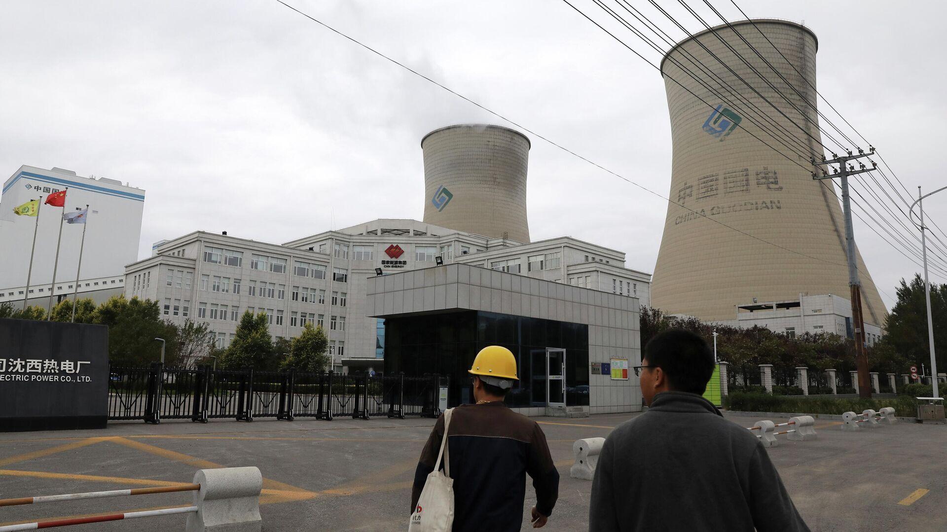 Unas personas caminan cerca a una central eléctrica de carbón en Shenyang, China - Sputnik Mundo, 1920, 10.10.2021