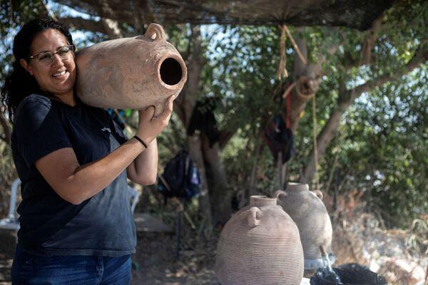 Una de las responsables de la excavación, Liat Nadav-Ziv, sostiene una jarra encontrada en el sitio. - Sputnik Mundo