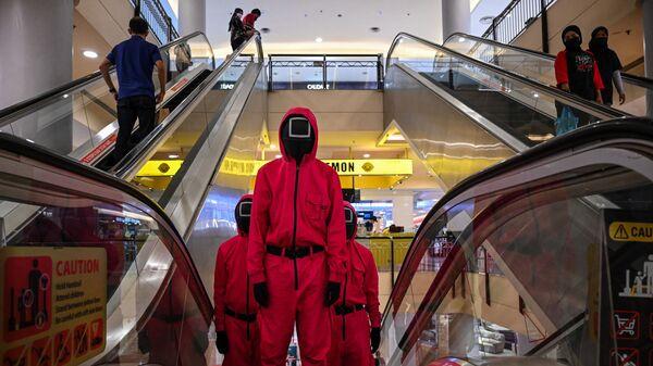 Косплееры в костюмах персонажей из сериала Netflix Игра в кальмара на эскалаторе в торговом центре Куала-Лумпура, Малайзия - Sputnik Mundo