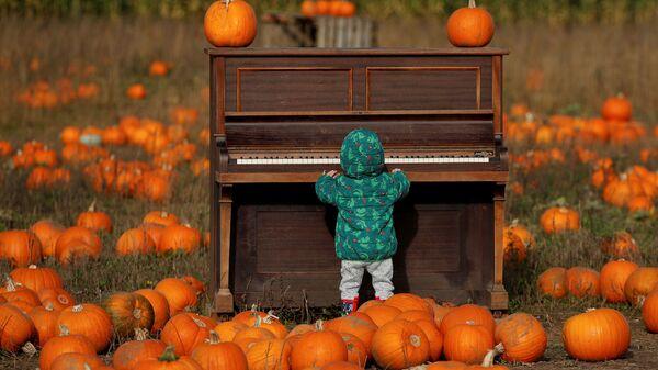 Ребенок играет на пианино на тыквенном поле фермы Pop Up Farm в Великобритании в преддверии Хэллоуина - Sputnik Mundo