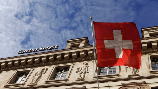 A national flag of Switzerland flies in front of a branch office of Swiss bank Credit Suisse in Luzern October 30, 2014 - Sputnik Mundo