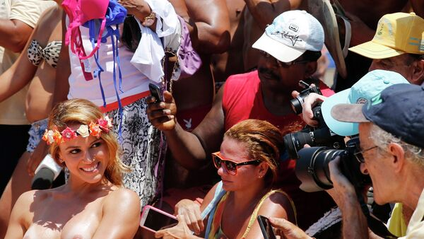 A woman poses with her top off as people take pictures during a protest called Make topless, not war at Ipanema beach in Rio de Janeiro January 20, 2015. - Sputnik Mundo