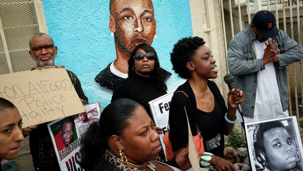 Demonstrators rally against the Missouri grand jury's decision to not indict Darren Wilson for his fatal shooting of Michael Brown, in front of a mural of Ezell Ford - Sputnik Mundo