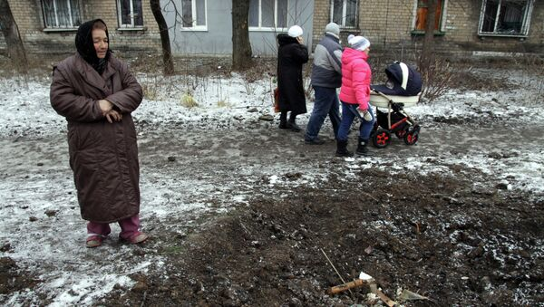A woman looks at a crater left in the ground after shelling in Makiivka, Donetsk region, on January 27, 2015 - Sputnik Mundo