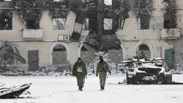 Fighters of the separatist self-proclaimed Donetsk People's Republic walk past a destroyed Ukrainian army armoured personnel carrier in the town of Vuhlehirsk, about 10 km (6 miles) to the west of Debaltseve, February 16, 2015 - Sputnik Mundo