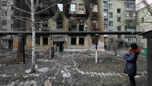 A woman looks at a building damaged by fighting in the city of Debaltseve, February 20, 2015 - Sputnik Mundo