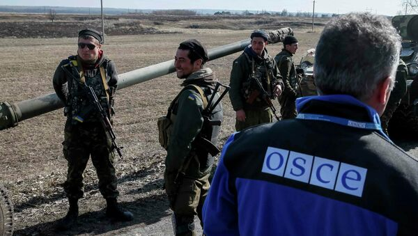 A member of Special Monitoring Mission of the OSCE to Ukraine walks along a convoy of Ukrainian armed forces in Blagodatne, eastern Ukraine, February 27, 2015 - Sputnik Mundo